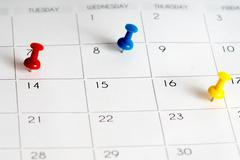 red blue yellow pins on calendar grid - stock photo