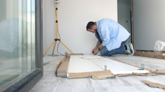 Young man matching pieces of furniture with screwdriver on floor at home Stock Footage
