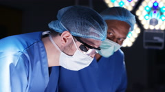 4K Surgeons operating on patient assistant wipes sweat from surgeon's face Stock Footage