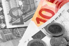 monochrome euro banknotes, coins, calculator - stock photo