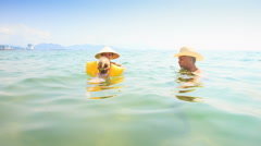 Little Girl in Armbands Swims from Mother to Grandpa in Sea Stock Footage