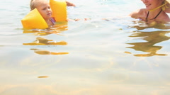 Little Girl in Armbands Swims away from Mom Grandpa in Sea Stock Footage
