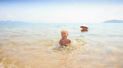 Little Girl Gambols on Sea Edge against Mom in Straw Hat Stock Footage