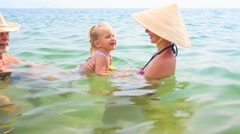Old Man Mother Lift up Little Daughter Play in Azure Sea Stock Footage