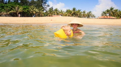 Little Girl in Armbands Swims from Mother to Azure Sea Stock Footage