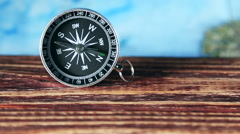 Compass on a wooden table and a map in the background Stock Footage