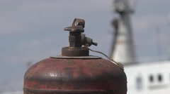Old gas cylinders are on the bank of river among steel ropes Stock Footage