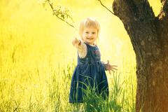 Little girl with great smile pointed with her finger at something happily Stock Photos