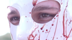 Murder mask with blood on it female eyes blink slow motion Stock Footage