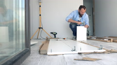 Young man matching pieces of furniture with hammer on floor at home Stock Footage