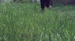 Person running through grass in slow motion Stock Footage