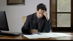 Absorbed business man studies his business presentation , playng with a pen Stock Footage
