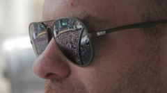Bald man watching a concert that is reflected on the lenses of his sunglasses Stock Footage
