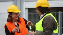 Male and female architects with safety jacket and yellow helmets drinking beer Stock Footage