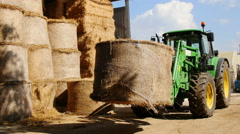 Tractor transports a big bale of hay Stock Footage