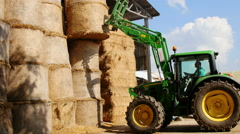 Tractor lifts bail of hay from barn Stock Footage