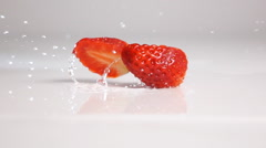 Sliced strawberry fall on white surface Stock Footage