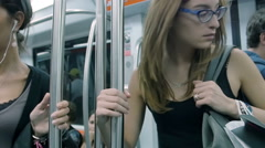 Young woman in the metro observing people around her Stock Footage