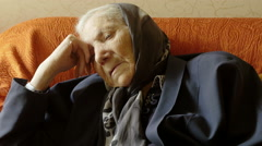 Little old woman thinks on orange sofa Stock Footage