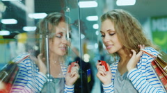 Shopping with a credit card. The girl in a glass storefront Stock Footage