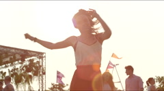 Close up of girl dancing at concert, sun flares Stock Footage