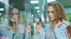 Attractive young woman looking at a glass display case in the store. The hands - stock footage