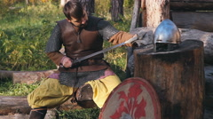 Warrior In Chain Mail Cleans Rubs Sword In Forest Stock Footage