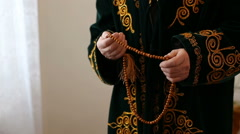 An old man in national dress praying with rosary beads in hands Stock Footage