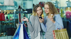 Two young women with shopping bags dyal go ice-cream and consider something on Stock Footage