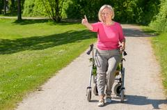 Elderly woman sits in wheeled walker on park path Stock Photos