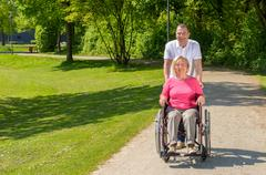 Elderly woman seated in wheel chair by husband Kuvituskuvat
