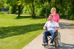Man seated in wheel chair while wife pushes Kuvituskuvat