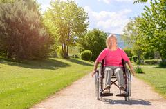 Elderly woman smiles while seated in wheel chair Kuvituskuvat