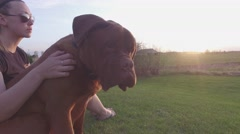 4k pretty woman petting her dogue de bordeaux at dusk Stock Footage