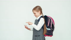 Portrait school girl 7-8 years with backpack using mobile phone on white Stock Footage