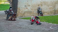 One knight is lying on the ground inside a castle - stock footage