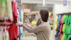 Young woman chooses clothes for a child Stock Footage