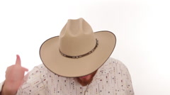 Hipster millennial cowboy putting on his cowboy hat with intense eyes - stock footage