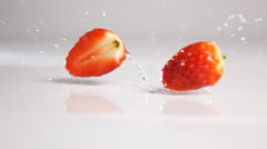 Sliced strawberry tumble on white surface Stock Footage