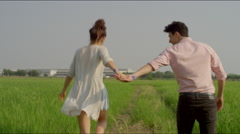 Couple hand in hand, skipping and  running - stock footage