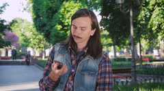 Young hipster man with mustache and long hair talking on phone in park Stock Footage