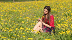 Model. Sitting among the blooming flowers of dandelion - stock footage