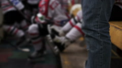 Team players sitting on the bench during hockey match, coach watching the game - stock footage