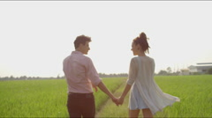 Couple walks, then hug and laugh  in rice field Stock Footage