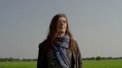 Long haired man walks through rice field Stock Footage