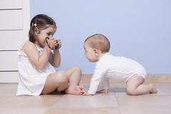 Pretty little sister taking pictures to her baby brother Stock Photos
