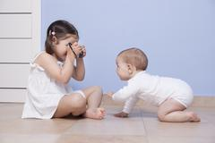 Pretty little sister taking pictures to her baby brother - stock photo