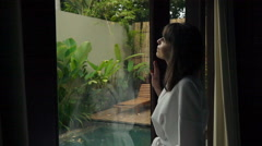 Pensive woman looking out of window during rainy day, super slow motion 240fps Stock Footage