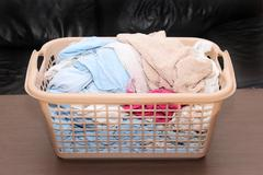 Clean wet laundry pile inside plastic basket - stock photo