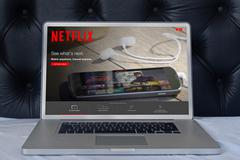 Netflix web page on laptop screen in the house bedroom - stock photo